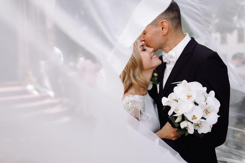 Foto Barbara - Fotografo economico a Torino - Sposi abbracciati con velo davanti e bouquet in mano alla sposa